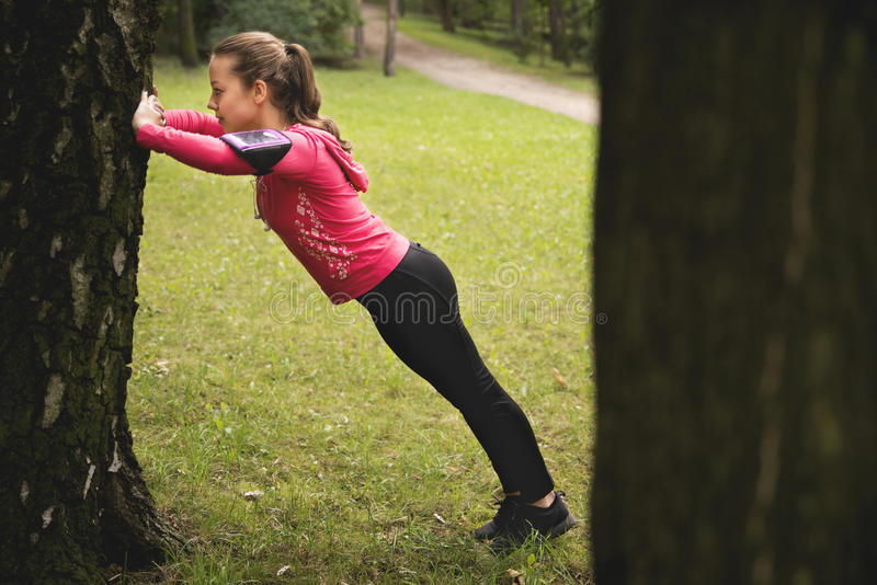 Young woman doing stretching exercises in a park royalty free stock images