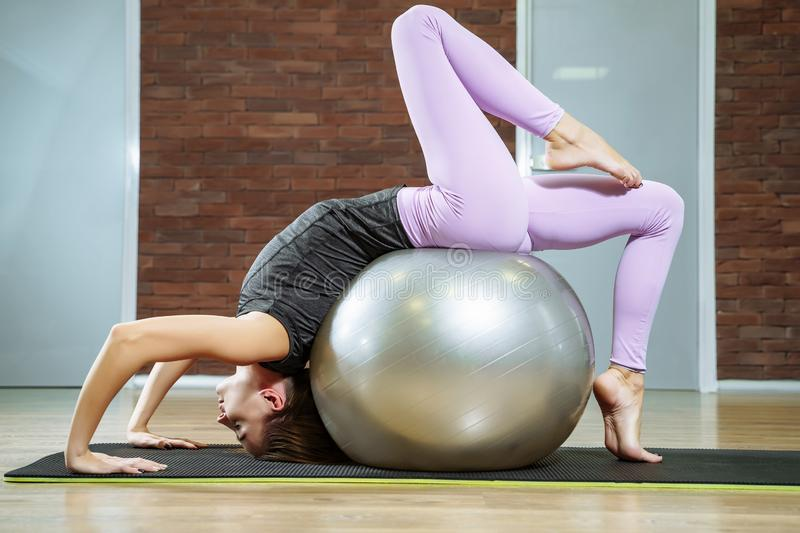 Young woman doing stretching using a fitness ball in the gym royalty free stock image