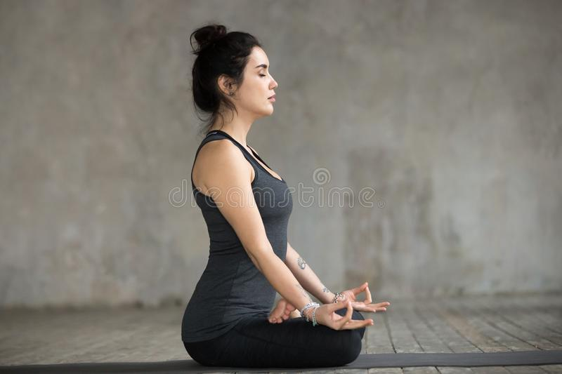 Young woman doing Sukhasana exercise, side view royalty free stock photo