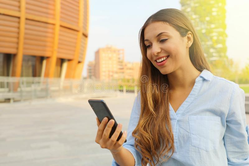 Young woman doing video call or texting on smart phone and walking in the street in a sunny day in Milan, Italy. Copy space royalty free stock photography