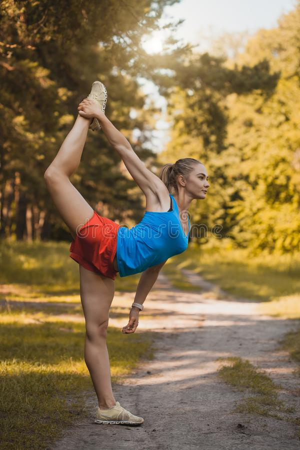 Young woman is doing warming up before running in the forest on a beautiful summer day stock image