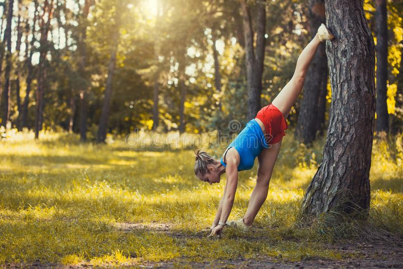 Young woman is doing warming up before running in the forest on a beautiful summer day royalty free stock photos