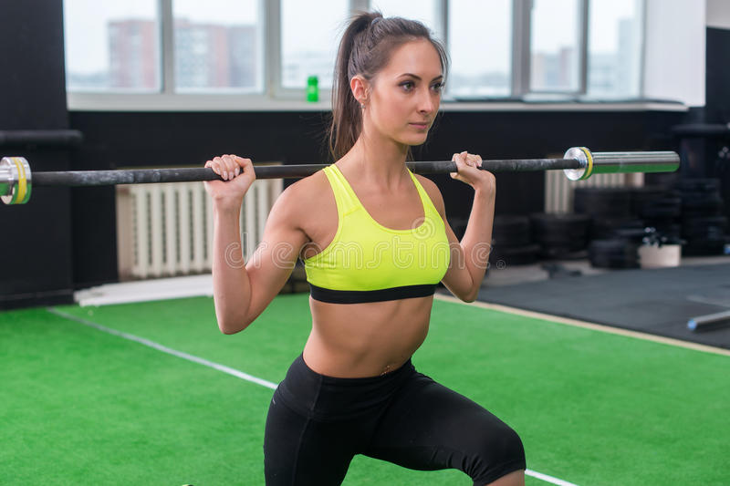 Young woman doing weightlifting exercises, athletic female squatting with barbell on her shoulders in gym stock photos
