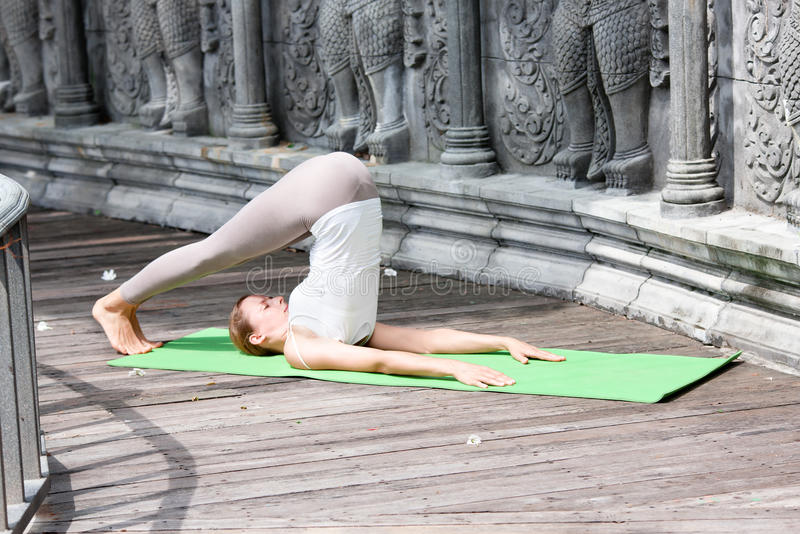Young woman doing yoga in abandoned temple on wooden platform. Practicing. stock photos