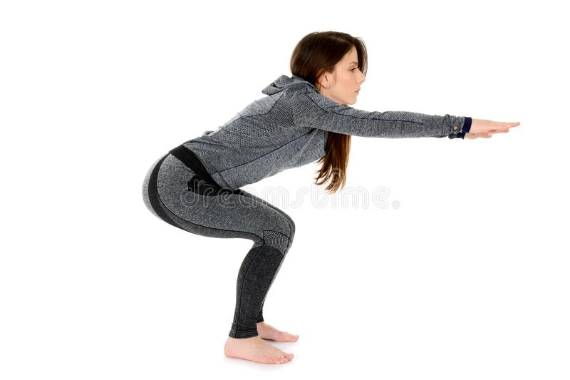 Young woman doing yoga asana Chair Pose or Standing Squat royalty free stock photo