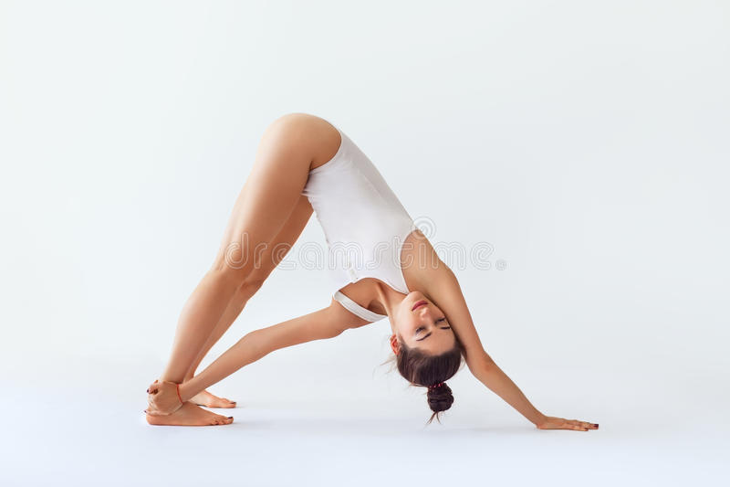 Young woman doing yoga asana revolved downward facing dog isolated on white background stock image