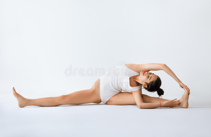 Young woman doing yoga asana revolved head to knee pose royalty free stock images