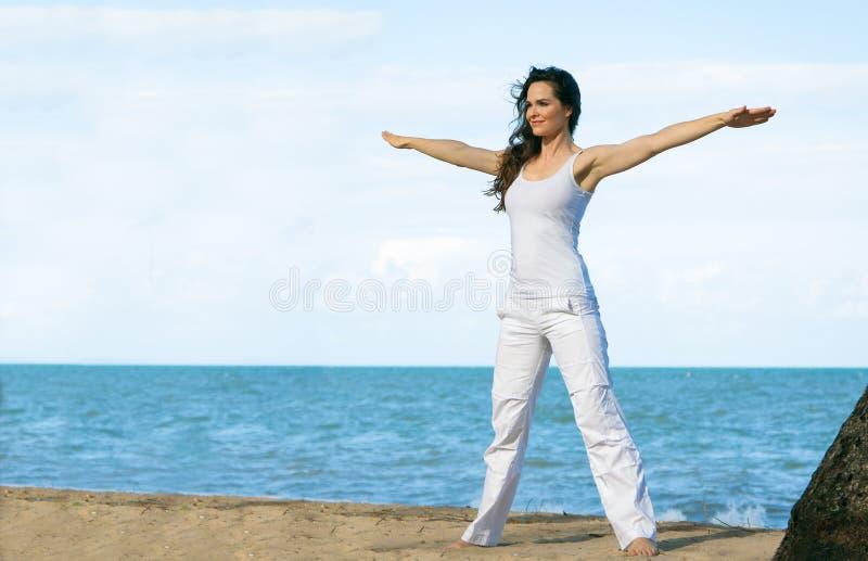 Young woman doing yoga on beach stock photos