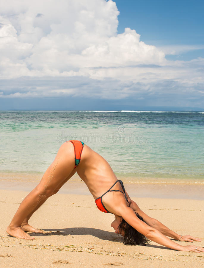 Young woman doing yoga on coast of sea on beach stock images