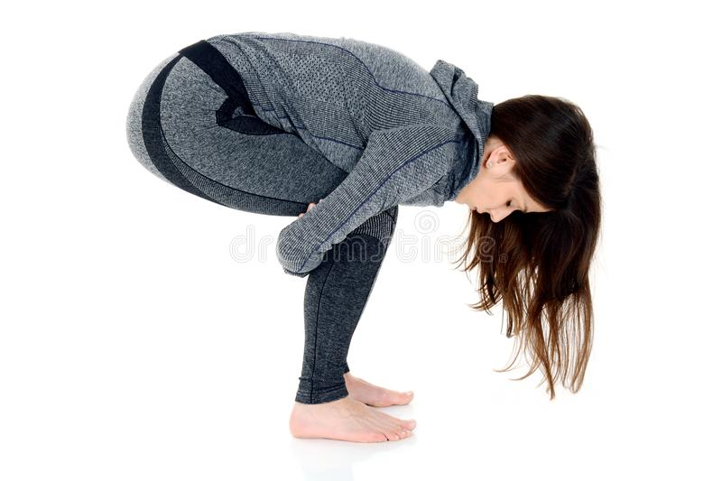 Young woman doing yoga exercise, squat position stock images