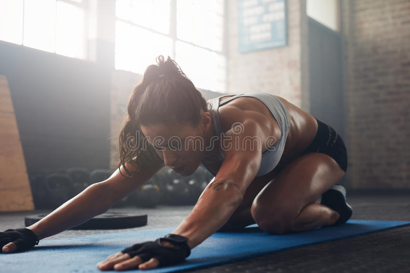 Young woman doing yoga on the gym floor. Shot of a young woman doing yoga on the gym floor. Muscular female doing stretching workout at health club royalty free stock photography