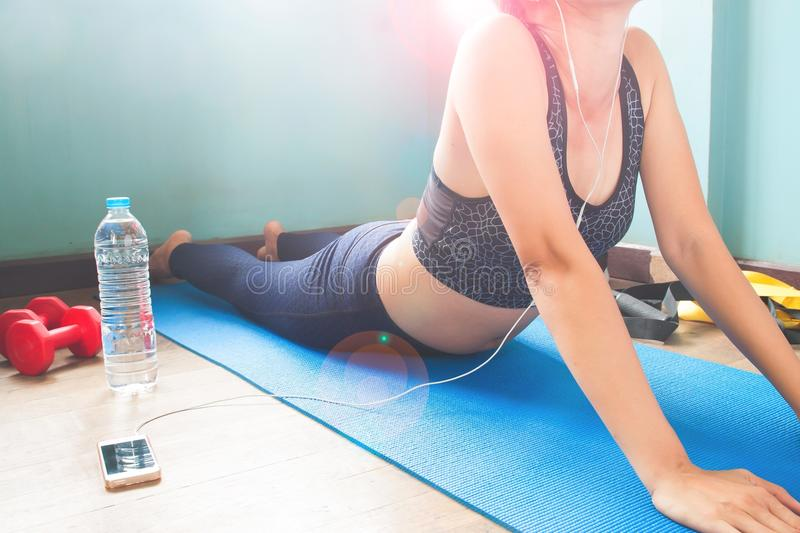 Young woman doing yoga at home and listening music from smartphone stock photos
