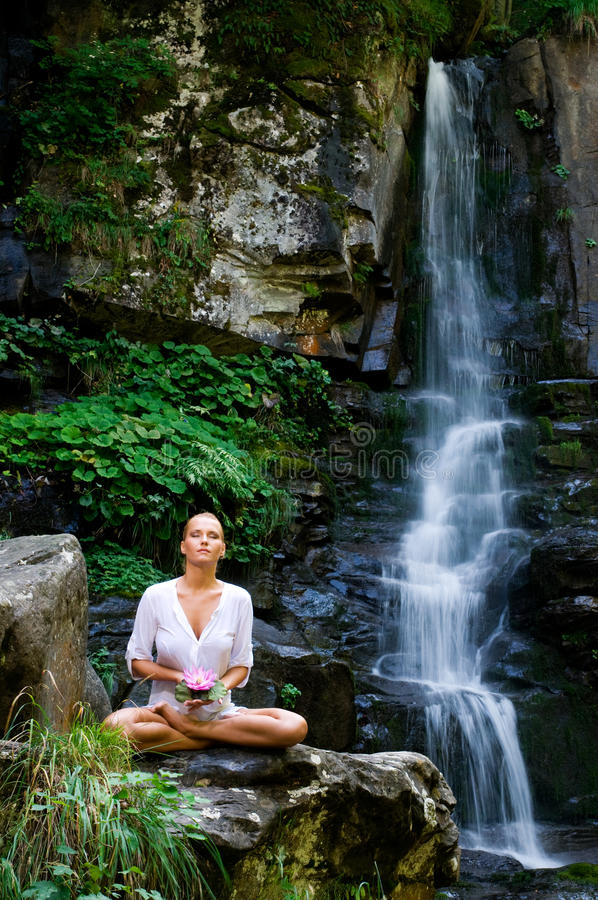 Young woman doing yoga with lotus flower stock photography