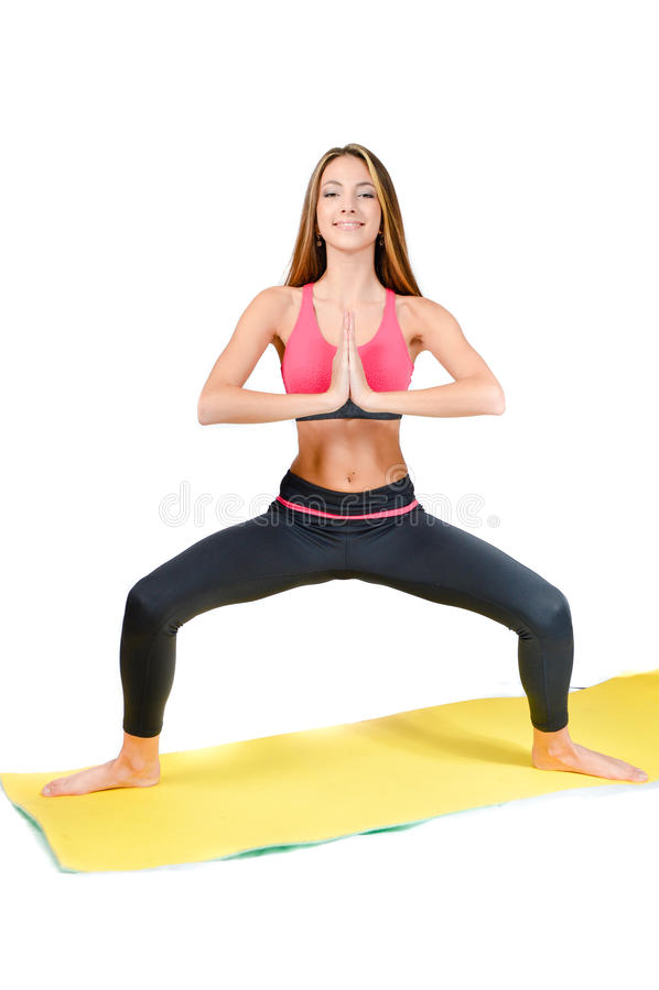 Young woman doing yoga on mat studio shot stock photography