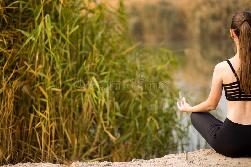Young woman doing yoga in morning park. Healthy lifestyle royalty free stock image