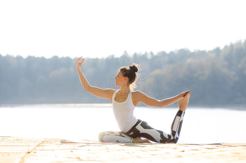 Young woman doing yoga near lake outdoors, meditation. Sport fitness and exercising in nature. Autumn sunset. Young woman doing yoga near lake outdoors royalty free stock photo