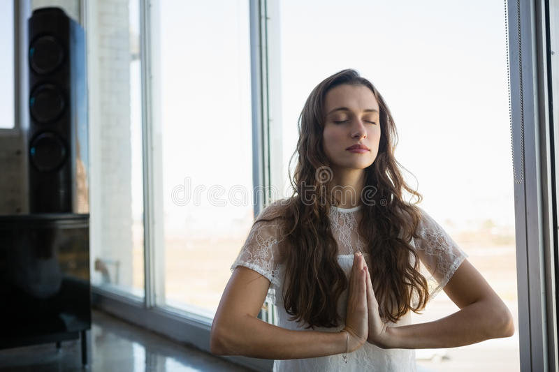Young woman doing yoga at office stock photography