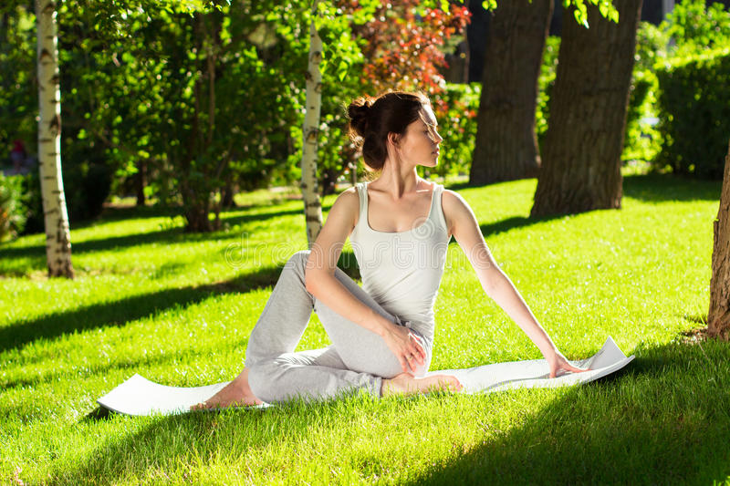 Young woman doing yoga in the park in the morning royalty free stock photo