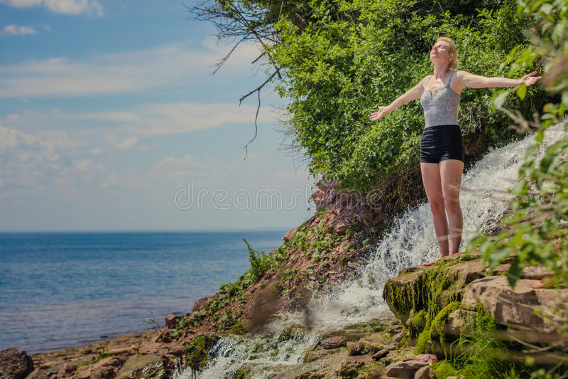 Young Woman doing Yoga Position Near a Waterfall stock photos