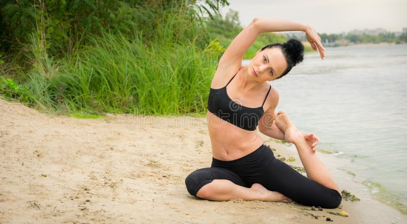 Young woman doing yoga on the river bank. City break royalty free stock photos
