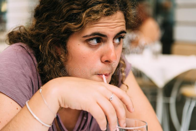 A young woman doubtful while drinking soda stock photography