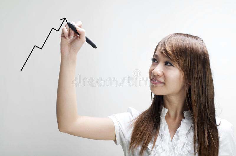 Young woman drawing graph. Closeup of young Asian business woman drawing graph on transparent glass or foil royalty free stock photo