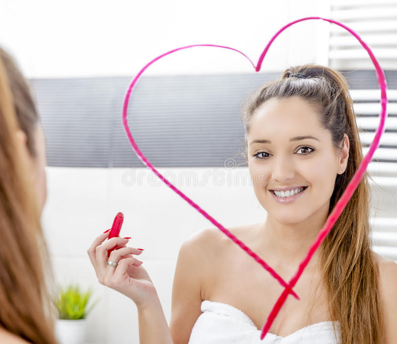 Young woman drawing heart to the mirror. In Valentines Day with lipstick stock image