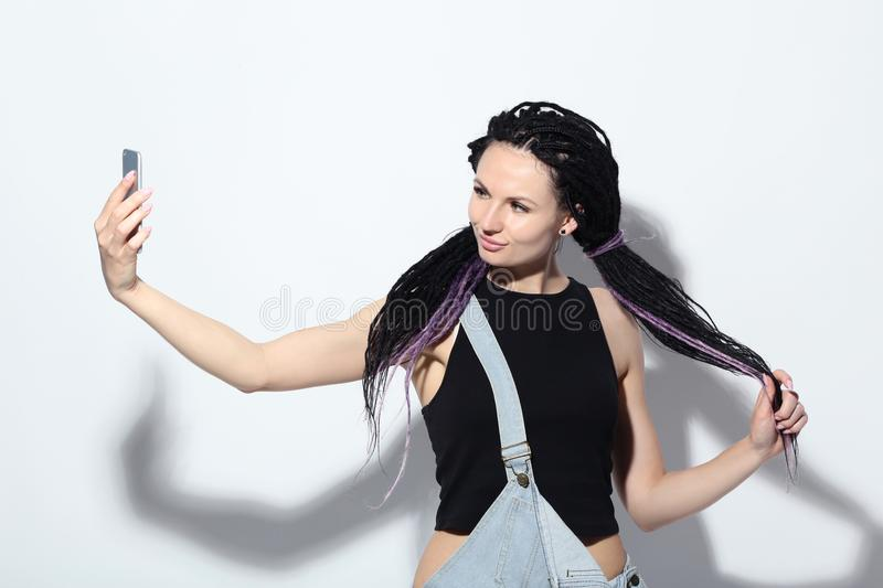 Woman with dreadlocks making selfie. Young woman with dreadlocks making selfie on white background stock image