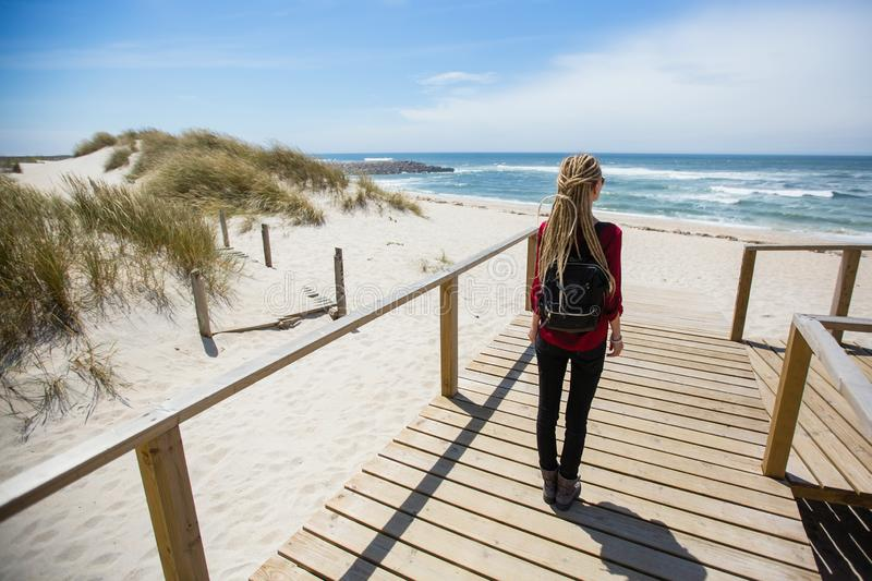 Young woman with the dreads is on the path to the ocean. Travel. stock images