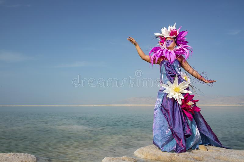 Young woman in a dress decorated with artificial flowers standing on a salty formation stock photos