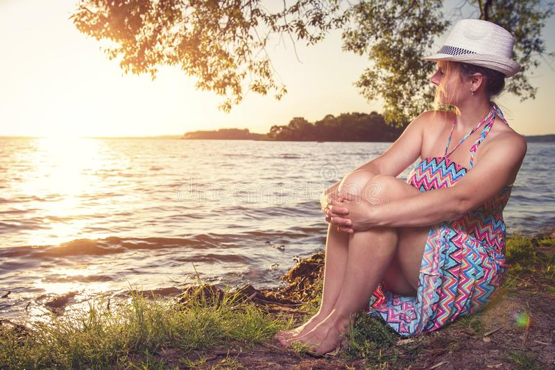 Young woman in dress and hat sits on lake shore under large tree and looks at sunset on horizon on warm summer evening royalty free stock photography