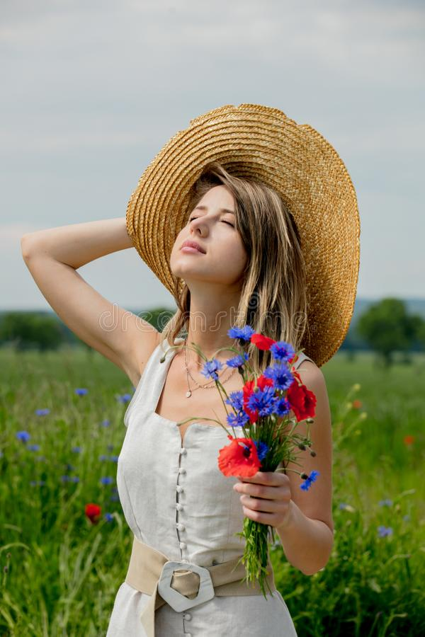 Young woman in dress and with hat stay near field with bouquet stock photography
