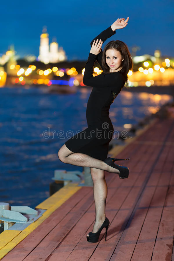 Young woman in dress standing on the waterfront stock photo