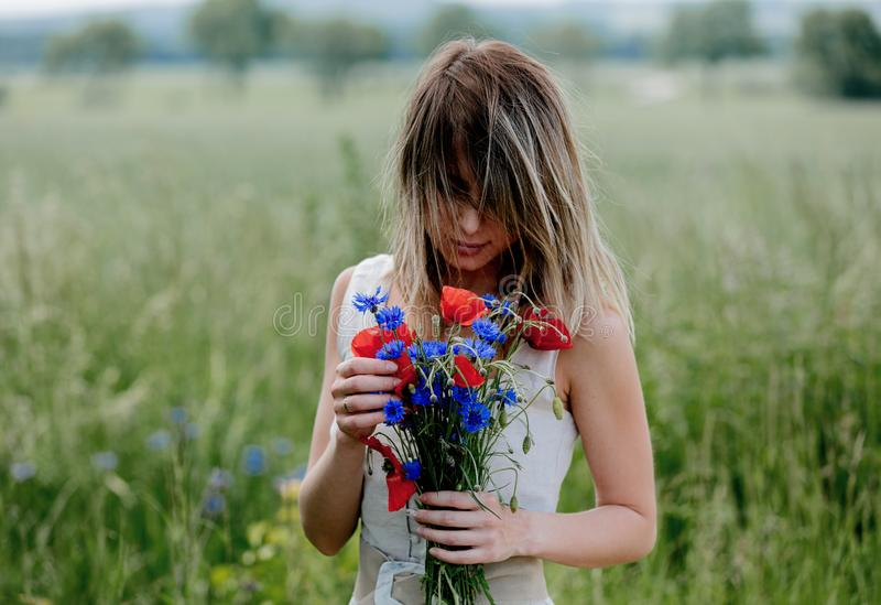 Young woman in dress stay near field with bouquet royalty free stock photos