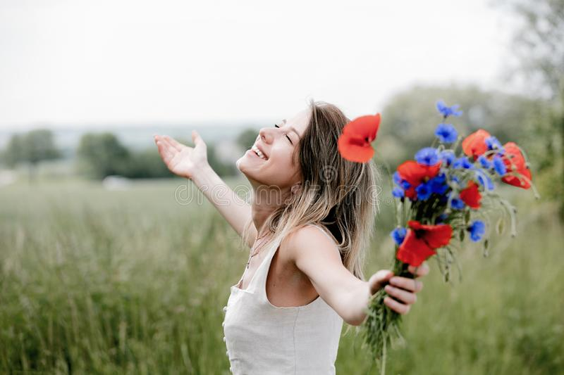 Young woman in dress stay near field with bouquet stock photo