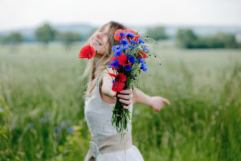 Young woman in dress stay near field with bouquet royalty free stock photo