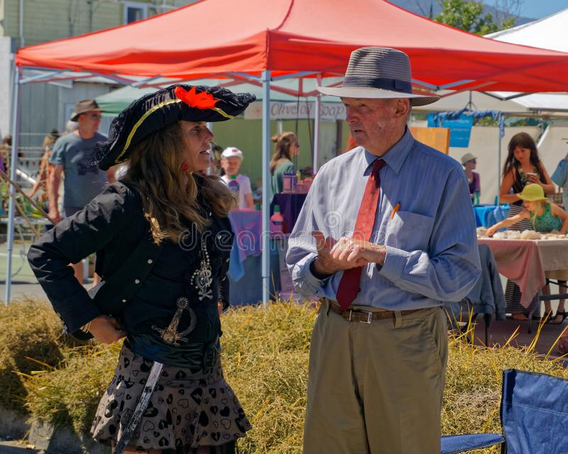 Young woman dressed as a pirate talking to an older gentleman on the Jehovah`s Witness market stall, Takaka market, Golden Bay, stock image