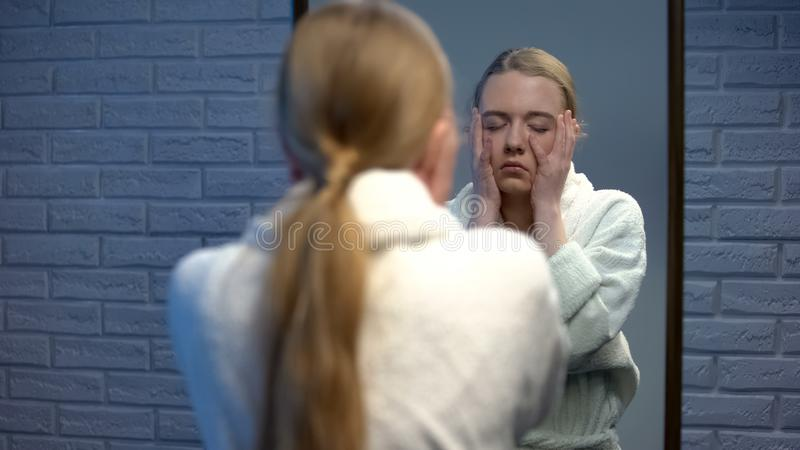 Young woman dressed in bathrobe touching face in despair, suffering depression royalty free stock photos
