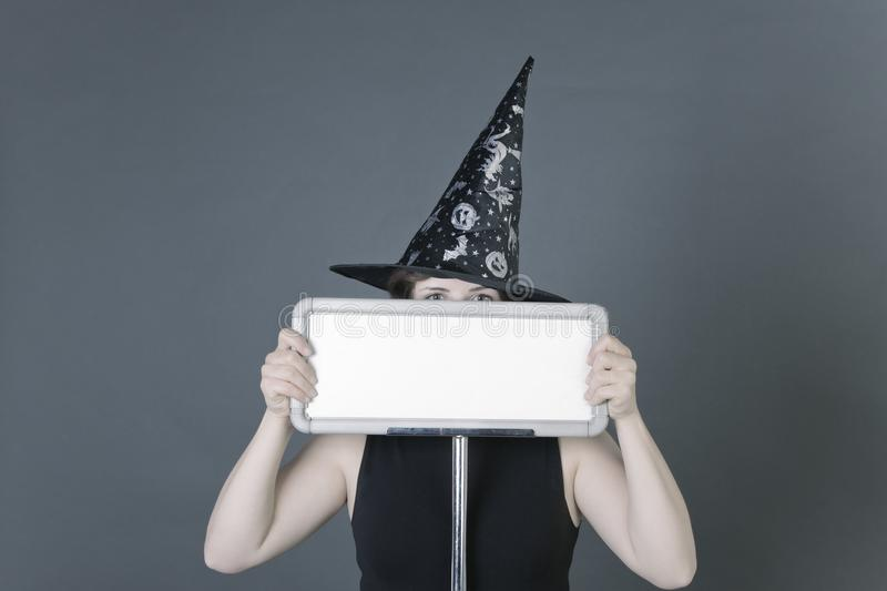 Young woman dressed in black pilgrim robe and hat holding a plain blank white sign on grey background royalty free stock images