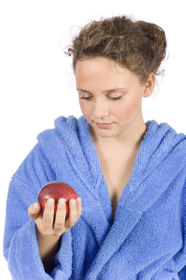 Young woman dressed blue bathrobe with an apple royalty free stock image