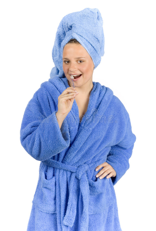 Young woman dressed blue bathrobe brushing teeth royalty free stock photography