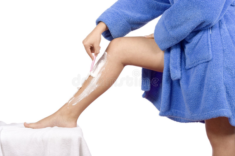 Young woman dressed blue bathrobe shaving leg royalty free stock photos