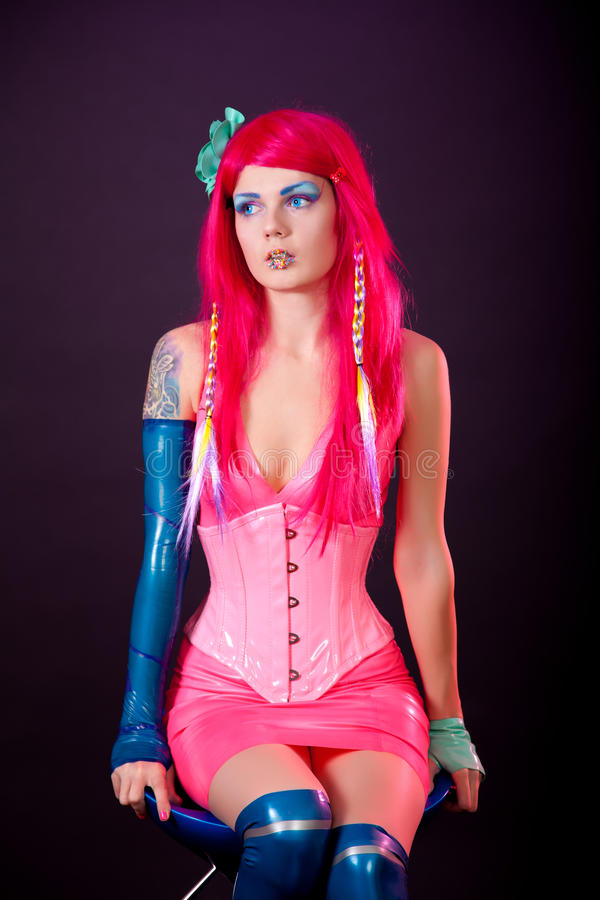 Young woman dressed in bright latex clothes stock images