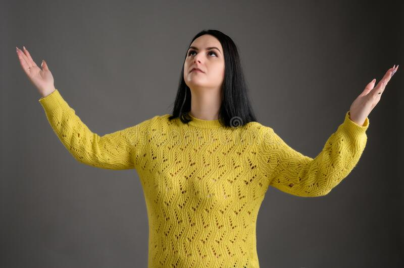 Young woman dressed casually thanks with open arms. Young woman with black hair dressed casually in a yellow sweater thanks with open arms, posing an isolated royalty free stock images