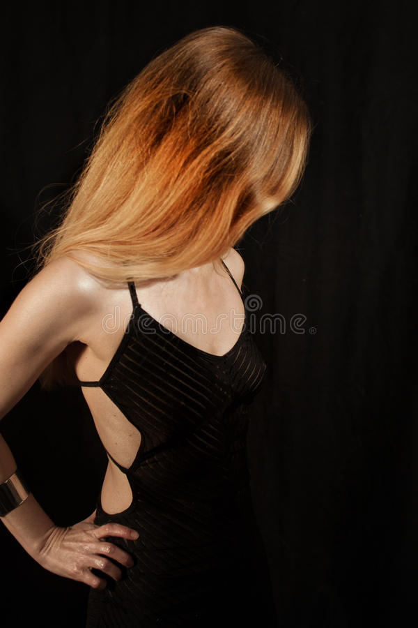 Young woman dressed in an elegant black evening dress stock photography