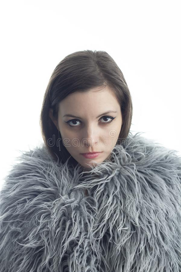 A young woman dressed in fur looks ahead royalty free stock photography