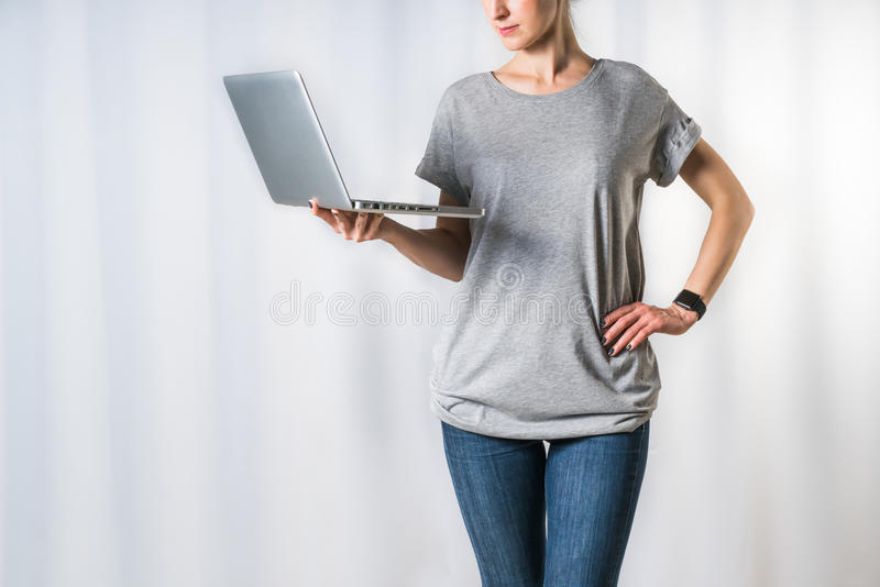 Young woman, dressed in gray t-shirt and blue jeans, standing on light gray background and holding laptop. Front view of young woman, dressed in gray t-shirt stock image