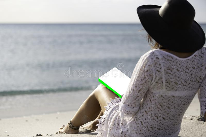 Young woman dressed in a white lace dress, white underwear and big black hat from behind sitting by the sea holding a book with royalty free stock image