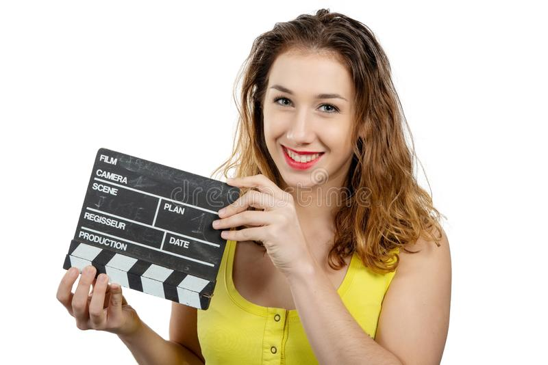 Young woman dressed in yellow with a movie clapper on white stock photo