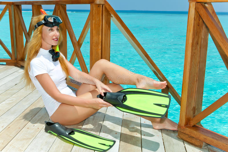 The young woman dresses equipment for underwater s royalty free stock photography